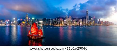 Panorama of Hong Kong City skyline with tourist sailboat at night. View from across Victoria Harbor HongKong. Stockfoto ©
