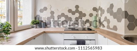 Panorama of kitchen in scandinavian style with white cabinets, wooden countertop and hexagonal wall tiles ストックフォト ©