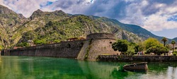 Panorama of Kotor Bay or Boka Kotorska, mountains and the ancient stone city wall of Kotor old town former Venetian fortress in Montenegro