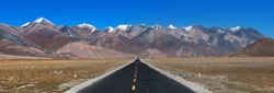 Panorama of landscape view of Tibet. Long & straight road ahead with high mountain range in front in the distance