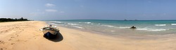 Panorama of lonely Nilaveli beach with yellow sand, turquoise water and boat on the beach, Eastern coast of Sri Lanka