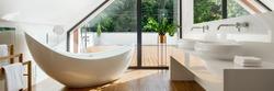 Panorama of luxury attic bathroom with beautiful bathtub and big window wall with balcony