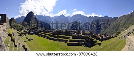 Panorama of Machu Pichu with Huayna Picchu in Peru, rainforest jungle and mountains with blue sky in the background