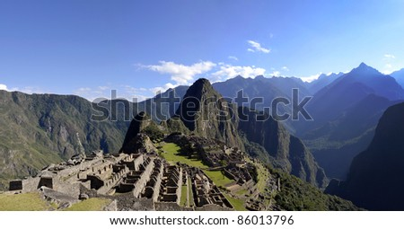 Panorama of Machu Pichu with Huayna Picchu, rainforest jungle and mountains with blue sky in the background