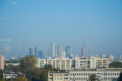 Panorama of modern buildings in Warsaw, Poland during sunny, warm day with blue sky and reflection through office window