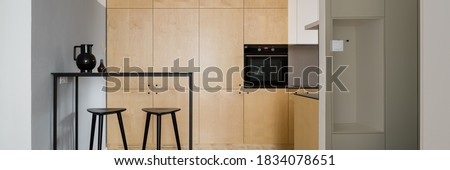 Panorama of modern style kitchen with birch plywood cupboards and black table with tall bar stools Foto stock ©