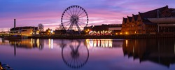 Panorama of Motlawa River and Ferris wheel with water reflection in Old Town of Gdansk at night, Poland