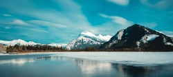 Panorama of Mount Rundle mountain peak with blue sky reflecting in Vermilion Lakes at Banff national park, Alberta Canada