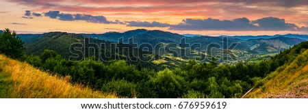 panorama of mountain ridge with peak behind the hillside. beautiful summer background at sunset with red sky