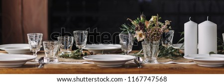 Panorama of noble lifestyle table decoration set for thanksgiving, precious glasses, floral decor, white candles, autumnal flowers, white porcelain on a long wooden table. Still life dinner, wood