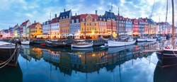 Panorama of north side of Nyhavn with colorful facades of old houses and old ships in the Old Town of Copenhagen, capital of Denmark.