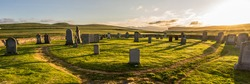 Panorama of old hillswick cemetery full of tombstones on the Shetland (Scotland, UK) on a magical sunset with dramatic warm light and a green meadow