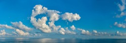 Panorama of peaceful blue sky with puffy white clouds. High resolution panoramic sky.