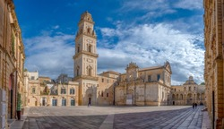Panorama of Piazza del Duomo square , Campanile tower and Virgin Mary Cathedral (Basilica di Santa Maria Assunta in Cielo), Caritas Diocesana in Lecce - Puglia, Italy. Baroque city of Apulia
