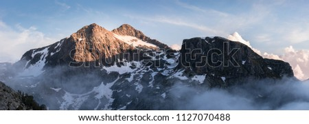 Panorama of Pic Negre de Joclar at sunset taken from near the Refuge de Rulhe on the GR10 hiking route. The snow scattered mountain is caught in the light with nearby mountains and clouds in shadow.