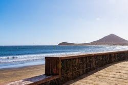 Panorama of popular place for windsurfing, kitesurfing and surfing on Tenerife. Touristic beach with for sport and activities. Rocks and mountain.