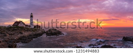 Panorama of Portland Head Lighthouse with the rising sun and colorful clouds