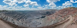 panorama of quarry extracting iron ore with heavy trucks, excavators, diggers and locomotives