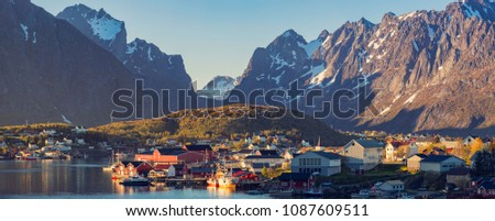 Panorama Of Reine Village on the Lofoten Islands, Norway. The Typical Norwegian fishing village  under midnight sun, blue sky, with the typical rorbu houses.  Mountain In Background