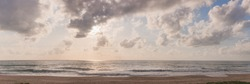 Panorama of rising sun on the horizon above a calm ocean or sea. On the blue sky white clouds.Nature and Summer Concept.