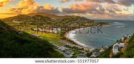 Panorama of Saint Kitts and its capital Basseterre during sunset, beautiful green mountains and a beach in paradise caribbean island with amazing green and orange colors