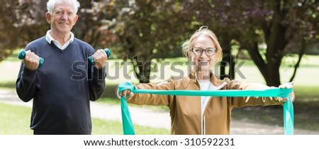 Panorama of senior sporty pair exercising on fitness trail