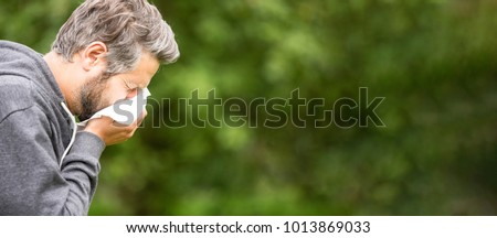 Panorama of sick or allergic man sneezing with tissue