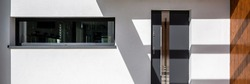 Panorama of simple front doors and long window in white facade house, exterior view