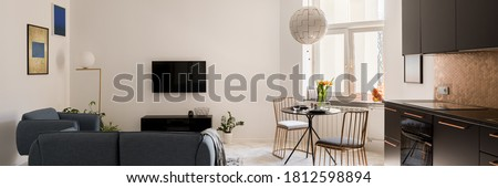 Panorama of small and designed apartment with elegant living room area, stylish dining table with new golden chairs and modern black kitchen in one room Stockfoto ©