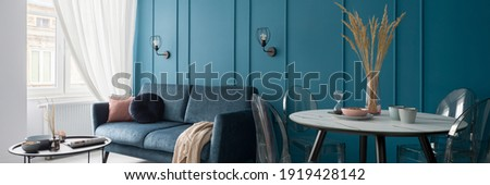 Panorama of small and nice designed living room with modern dining table and stylish blue wall with molding Stockfoto ©