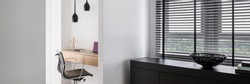 Panorama of smart home office with wooden desk in recessed wall niche behind white wall next to black chest of drawers under window with black blinds