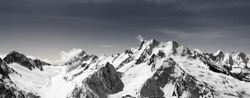 Panorama of snow-capped mountain peaks and sky with clouds at sun windy day. Caucasus Mountains in winter, region Dombay. Black and white toned landscape.