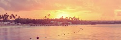 panorama of sunset beach of La Romana, Dominican Republic with long wooden pier