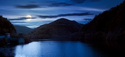 panorama of tarnita lake in romania at night. beautiful nature scenery in autumn in full moon light. gorgeous sky with glowing clouds