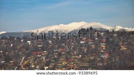 Panorama of Tatra Mountains and colourful houses on their slopes. Liptovsky Mikulas, Slovakia.