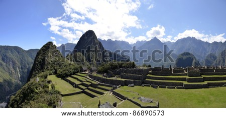 Panorama of Terraces Machu Pichu with Huayna Picchu in Peru, rainforest jungle and mountains with blue sky in the background