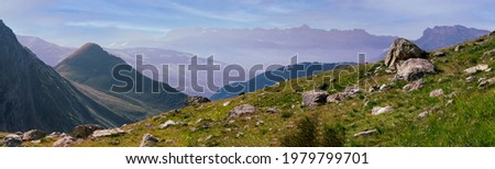 Panorama of the Alpine mountains. Ridges and peaks are visible in the background. Large and small stones lie on the grassy slope. Stock fotó ©