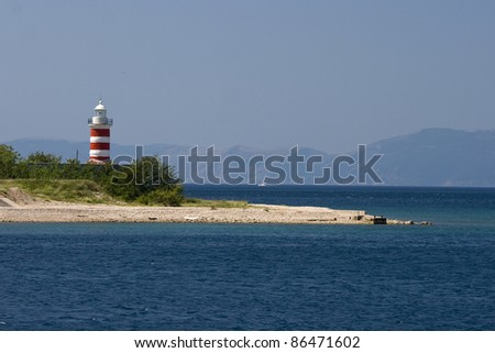 Panorama of the bay with the blue sea, land, island and the lighthouse