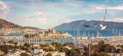 Panorama of the Bodrum port with seagulls over sea, ancient fortress and islands. Marine landscape with mooring sailboats and yachts on the Aegean Sea coastline in Turkish harbour.