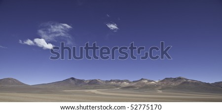 panorama of the Bolivian altiplano a sand desert at high altitude surrounded by mountains sunny day blue sky white clouds, copy space