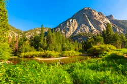 panorama of the californian excursion hike, Zumwalt Meadows hiking in Kings Canyon National Park, a large clearing in the forest with wildflowers and granite cliffs of Grand Sentinel obelisk rock.