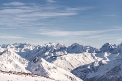 Panorama of the Caucasus mountains from Elbrus. Peaks of the sharp mountains from the highest mountain in the area. Mountains around Elbrus from a height of 4500 meters.