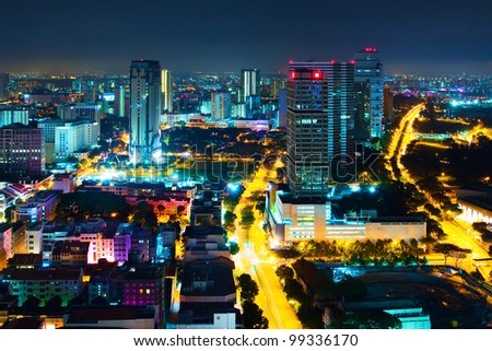 Panorama of the city at night, with low houses and high-rise business centers in the artificial lighting of streets (Night view of Singapore city - downtown)