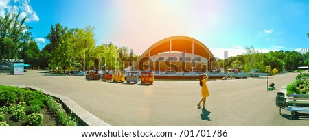 Panorama of the city park with a summer theater and a lake.A tall girl in a yellow dress photographs a panorama of a tall old theater building on the lake shore.Hot, sunny summer