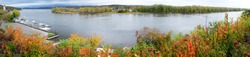 Panorama of the Hudson River in the fall. The river is curved infront are autumn trees on the left are pleasure boats moored and an island in the middle filled with autumn trees Hudson, New York, USA