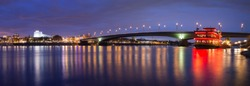 Panorama of the illuminated Kennedy Bridge and the river Rhine in blue hour after sunset in Bonn, Germany