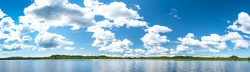 Panorama of the northern lake with blue sky and clouds