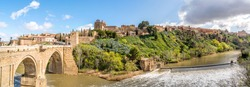 Panorama of the old historical city of Toledo with the bridge Puente de San Martín on the left and the river Rio Tajo in front. Toledo, Spain