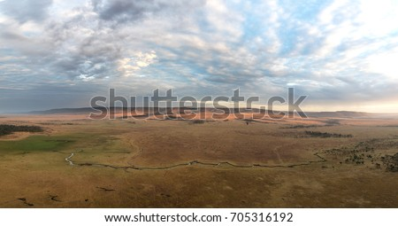 Panorama of the open plains of the Masai Mara at daybreak, with the Mara river and the hills of the Oldoinyio escarpment. Aerial view from a balloon. Hot air balloons can be seen in the distance.