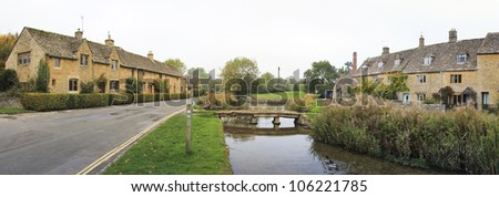panorama of the river eye winding through the quaint village of lower slaughter in oxfordshire england past cottages built in traditional cotswalds stone